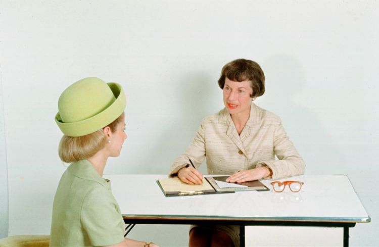 A young woman sits accross from an older woman who has a notebook. Both are wearing old fashioned dress. It looks like a job interview.