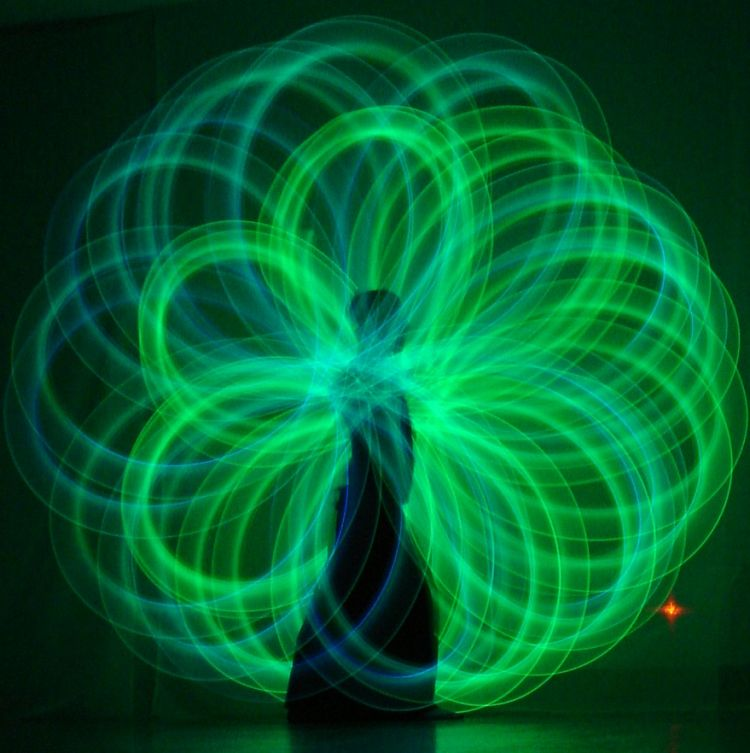 green poi circles, in a beautiful light pattern, around a woman