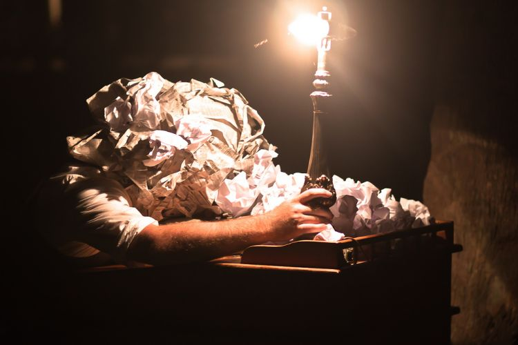 man covered in screwed up pieces of paper, slumps over desk holding onto a lamp